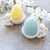 Colorful Easter Eggs in stand with ceramic easter bunny figurines and spring blossom on grey concrete background
