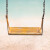 vintage color tone style of yellow swing on sand sea beach summer day